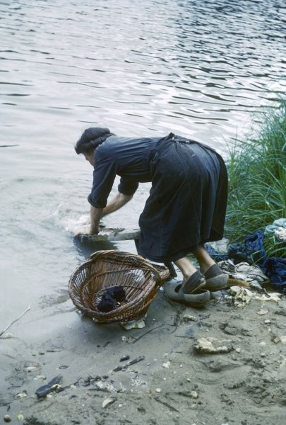A woman washes clothes in a river, using a washboard