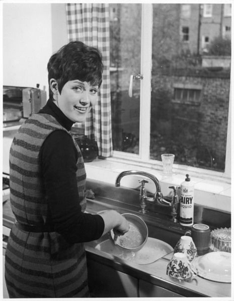 Sparkly housewife in a black polo neck sweater and sleeveless dress stands at the sink and washes up pans and cups in 'mild green Fairy Liquid&#39