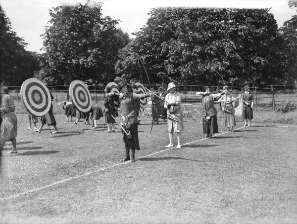 Standing in a row, several ladies practice their aim outdoors