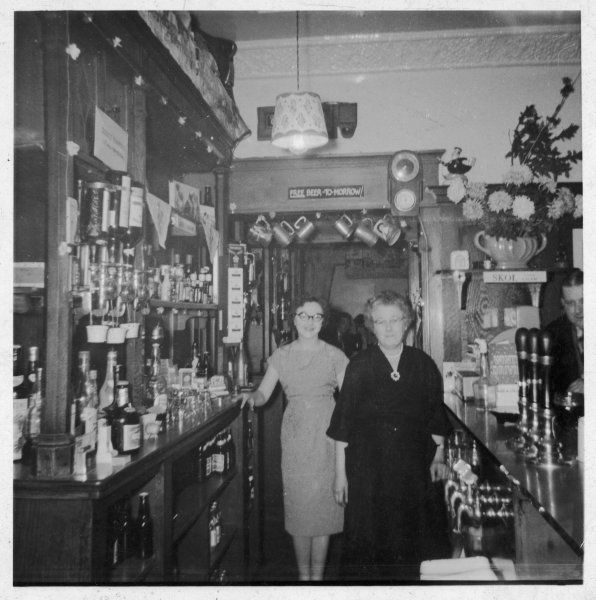 Two middle-aged women stand behind the bar in a pub