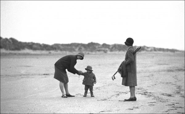 Two women with a child and golf clubs on a beach in Devon