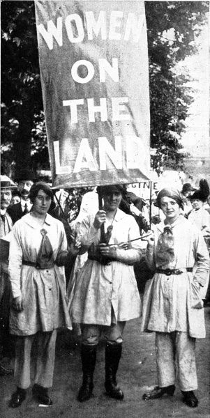 Three female agricultural workers are pictured with a banner. The women were taking part in a procession through London in July 1916 celebrating the many different roles of women throughout the First World War