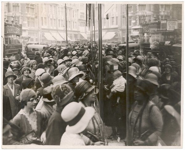 A crowd of women in cloche hats clamour to get into the Sales at a central London shop