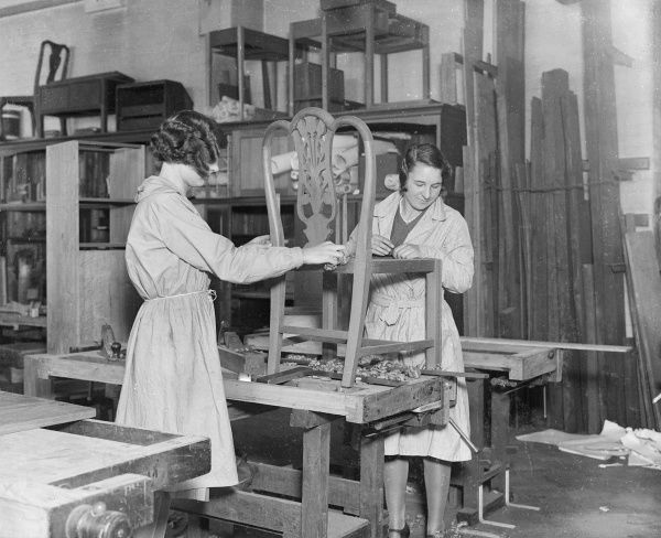 Young women carpentry students at the London County Council Trade School learning how to upholster a chair. Date: 1930s