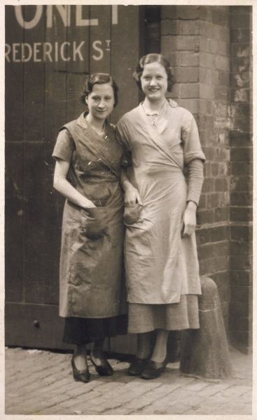 Two female workmates pose outside the factory gates at Burroughs & Sturgess, Frederick Street, Derby