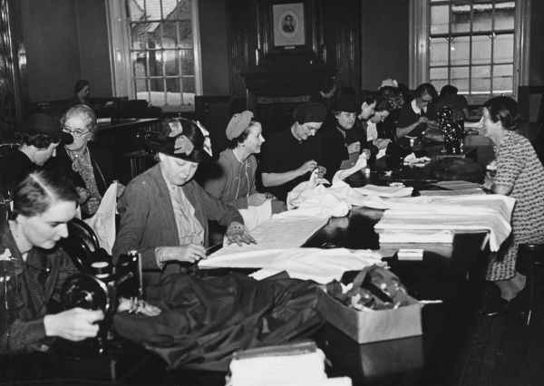 At Chelsea Town Hall, Lady Musprett is in charge of the sewing circle of Voluntary Workers who are here making black curtains and towels for use in the refugees' billets during World War II
