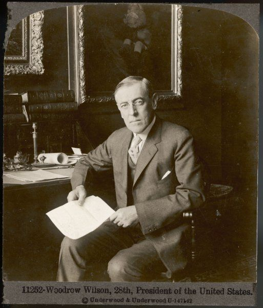 WOODROW WILSON 28th President of of U.S seated at his desk and holding a document