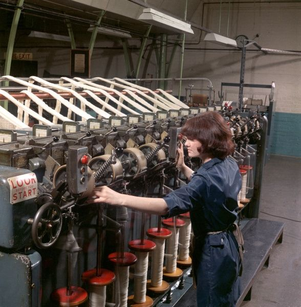 A woman worker in dark blue overalls operating and checking a huge wool-winding machine at Patons & Baldwins factory at Darlington. Patons & Baldwins was one of the largest manufacturers of knitting yarn in the UK between the 1970 and the 1980s