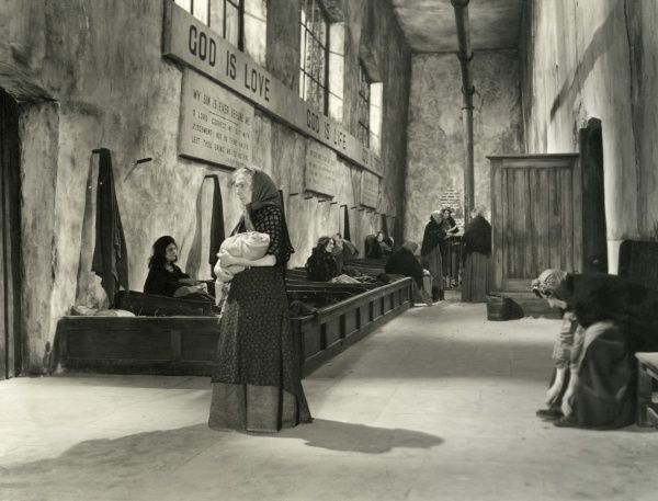 "A workhouse interior from the 1948 film of Oliver Twist, directed by David Lean. A female inmate carries a baby. Behind her are workhouse ""coffin beds"". On the walls are biblical quotations, including ""God is Love&quot"