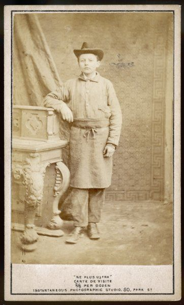 A working boy wears a felt hat, lightweight jacket in a coarse fabric, trousers, boots & a coarse apron