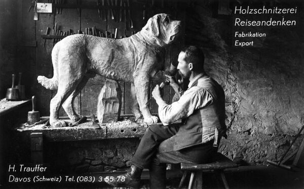 The carpentry workshop of carpenter H. Trauffer of Davos, Switzerland, pictures carving a fabulous life-size Saint Bernard dog. Date: circa 1920s