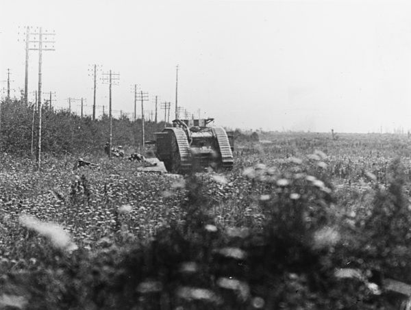 Canadian troops skirmishing with a tank on the front line to sort out an enemy machine gun post near Lihons on the Western Front in France during World War I in August 1918