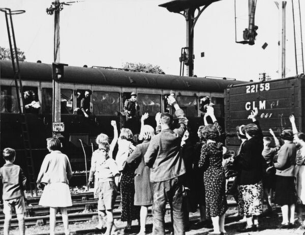 Evacuee train leaving the station with people waving goodbye during World War II
