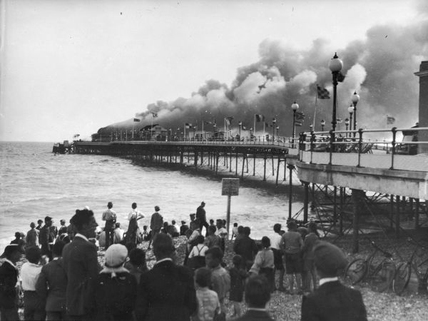Crowds watch the terrifying spectacle of Worthing Pier Pavilion ablaze. The flames and smoke could be seen for miles and the pier was completely destroyed
