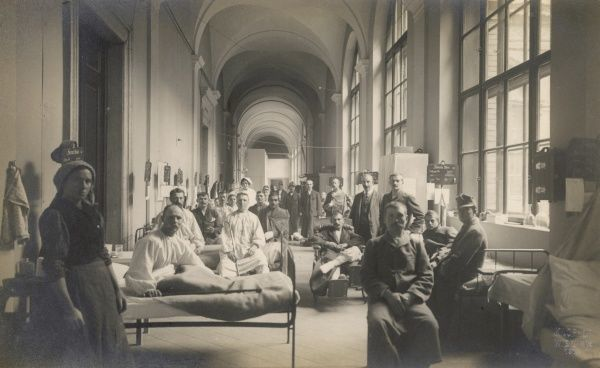 Wounded Austrian soldiers and their nurses during the First World War. They are in a corridor of the University of Vienna, which has been converted into a hospital ward. Date: 1914