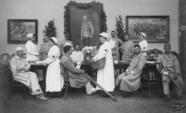 Wounded Austrian soldiers and their nurses, watched over by a portrait of Emperor Franz Josef I, during the First World War.  1914