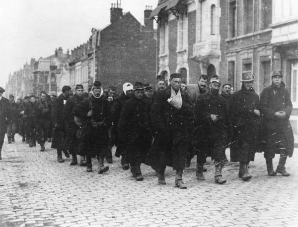 Wounded Belgian troops from Furnes, marching through Calais, north western France, during the First World War. Date: 11 November 1914