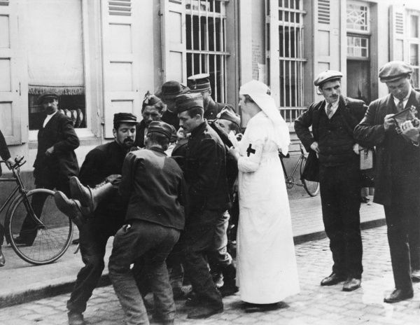 Tending a wounded man in the street at Malines, Belgium, during the retreat to Antwerp, First World War. He is carried by soldiers, under the supervision of a nurse. Date: 1 September 1914