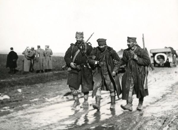A wounded soldier is helped along a muddy road by two colleagues on the Macedonian Front during the First World War. Date: circa 1916-1917