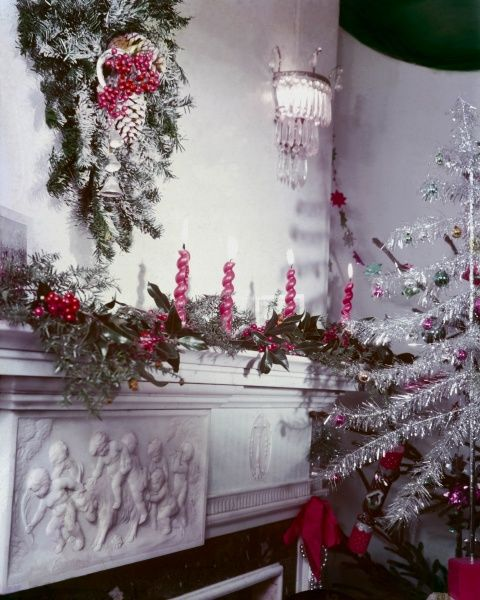 Festive wreath of fir with cones, imitation snow & red berries, a tinsel Christmas tree with baubles & red lighted candles & holly draped along the mantelpiece