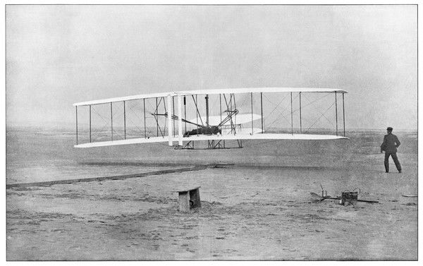 Orville Wright, watched anxiously by his brother Wilbur, achieves the first powered flight at Kitty Hawk, North Carolina