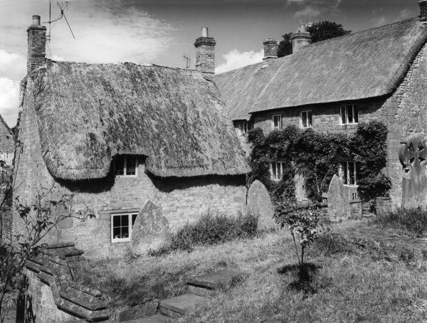 Fine thatched cottages in a picturesque corner of Wroxton, Oxfordshire, England. Date: 1960s