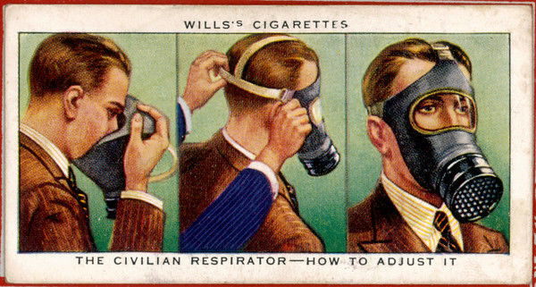 A man demonstrates how to put on a gas mask