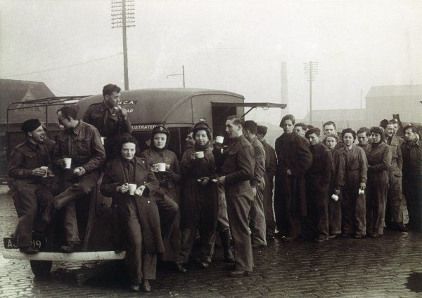 A group of women of the A.T.S., along with members of the army, queue at a refreshment van and enjoy a cup of tea during a break from work