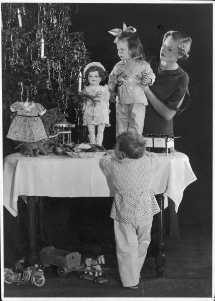 Mother lifts her daughter onto the table to admire the tree, beautifully decorated with candles and toys. Her little son stands by the table in admiration.. bedtime looms