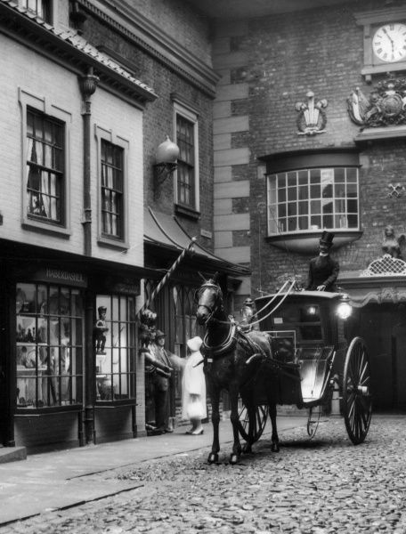 A re-created early 19th century cobbled street scene, with coach and dummy horseman outside a haberdashery. York Folk Museum, York, Yorkshire, England. Date: 19th century (re-enactment)