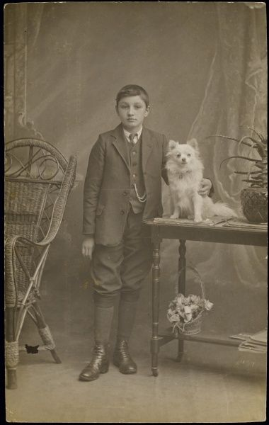 A young man poses with his pet Pomeranian for a studio portrait