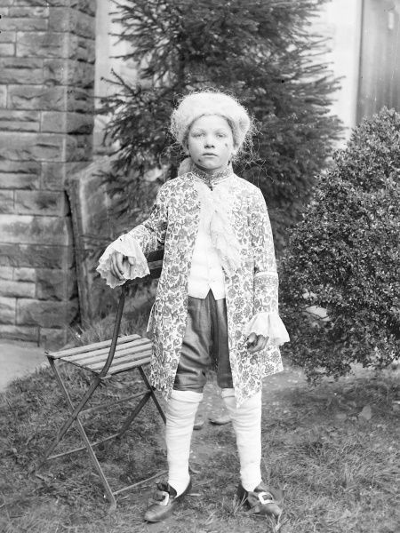 A young boy wearing Georgian costume poses for his photo in a garden in Mid Wales. He is leaning against a folding metal chair