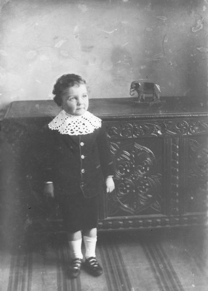 An angelic young boy stands before a finely carved chest in a satin suit with short trousers and sandals