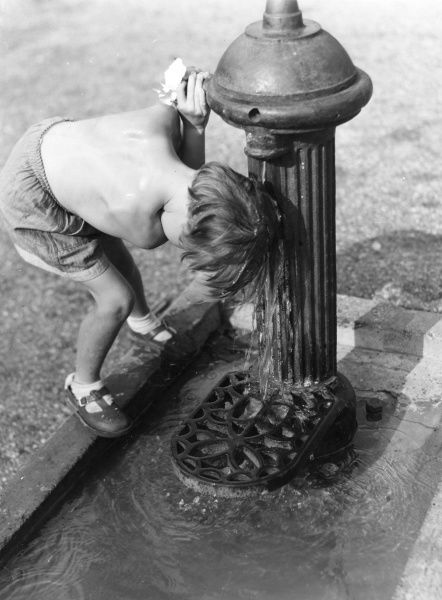 A young child operates a large cast iron water hydrant in order to pour water over his/her head on a hot summers day