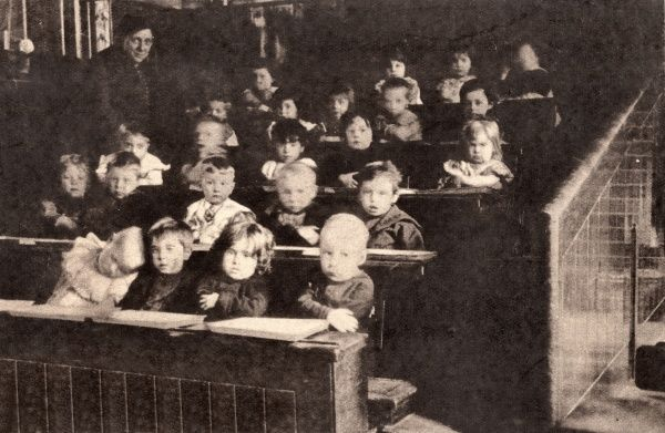 A class of young children in an elementary school. The desks are in banked rows. Their teacher stands at the left. A child on the front row has fallen asleep