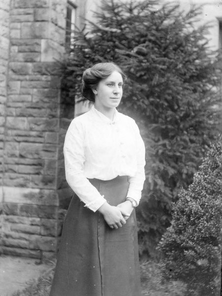 A young Edwardian woman standing in a garden, Mid Wales. She is wearing a white blouse and a plain dark skirt
