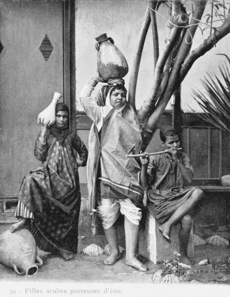 Two young Egyptian Arab girl water carriers stand behind a seated young boy playing his flute