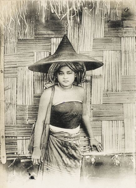 Young Girl from Burma (Myanmar) standing in front of a stunning woven reed wall