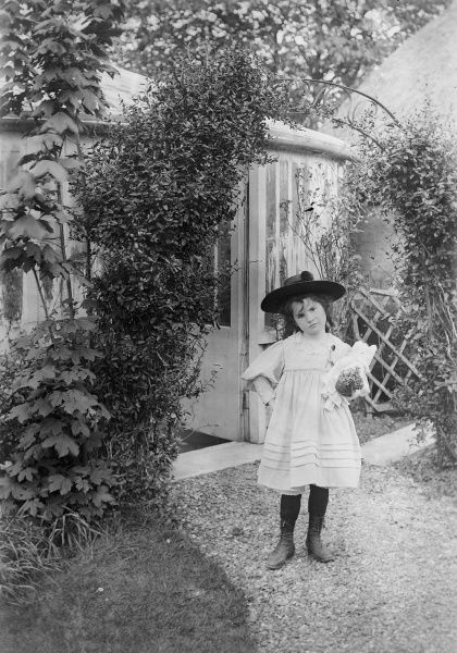 A young girl stands with hand on hip looking less than impressed, clutching her dolly, on a path in the garden of a large country house