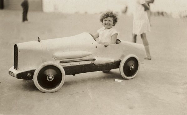 A happy young girl sits in a beautifully-made model of a vintage racing car