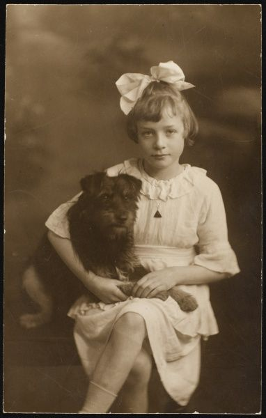 A young girl with her bobbed hair tied with a ribbon, poses with her pet dog, possibly a mongrel or terrier of indeterminate breed