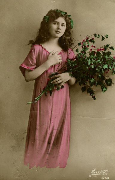 A young girl in a bright pink dress, holding a bunch of leaves and flowers.  1920
