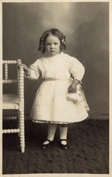 Unnamed young girl in pretty white dress, standing by a white armchair with bobbled scrolling on the turned arms and legs. Date: circa 1903
