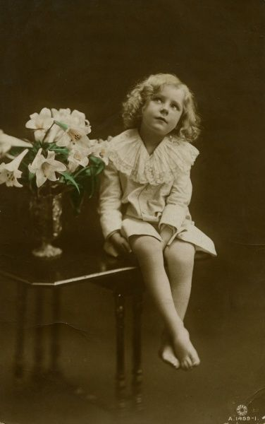 A young girl in a frilly white dress, sitting on a table next to a vase of flowers.  1915