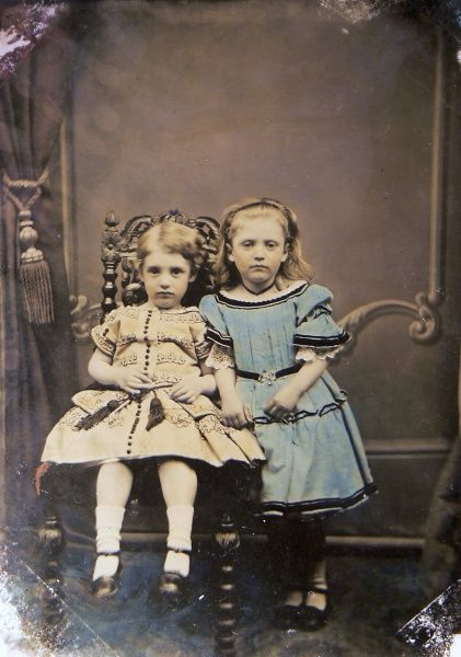 Two rather sullen young girls in their finest frocks pose for a photograph