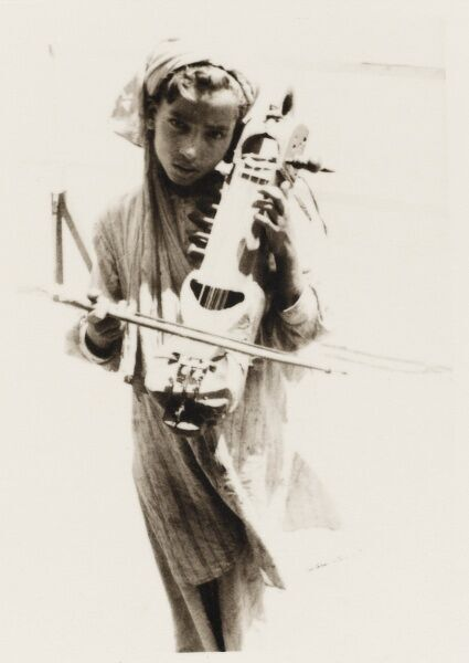 A young Indian girl playing a traditional bowed stringed instrument
