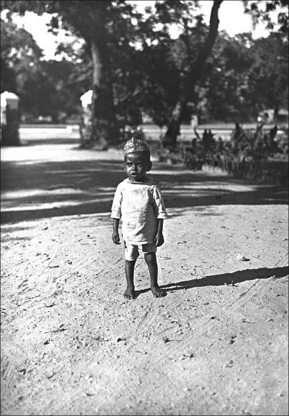 A young Indian toddler standing in the middle of a dusty road. Photograph by Ralph Ponsonby Watts