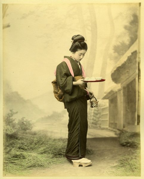 A young Japanese woman in traditional dress carries a tray containing small cups of tea