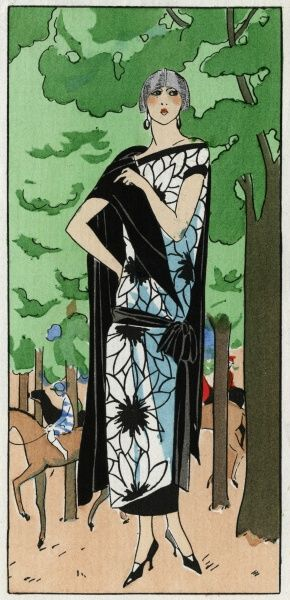 Young lady wearing a 3/4 length white dress in crepe de chine with large black floral design and black cape, by Lucien Lelong. Racehorses and jockeys can be seen between the trees in the background.  1924