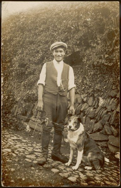 A young man in waistcoat and cap stands with his dog, holding something which is probably a rabbit-trap